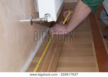 Skirting Board & Architrave. Repairman's Hands Installing Skirting Board Oak Wooden Floor. Measuring
