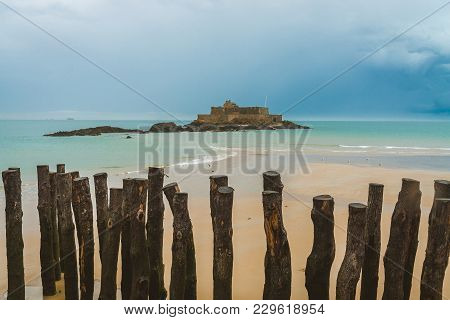 Wooden Poles On Beach In Front Of 17-century Fort National On Island Petit Be During Low Tide In Sai