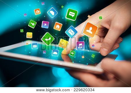 Businessman hand using tablet with flying application icons around