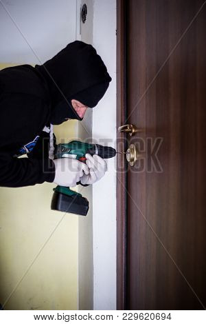 Crime, Robbery, Masked Thief, Burglar, Trying To Break Into A Flat, A Drill In The Hands, A Cap On T