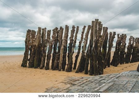 Wooden Poles On Beach During Low Tide In Saint-malo, Brittany, France