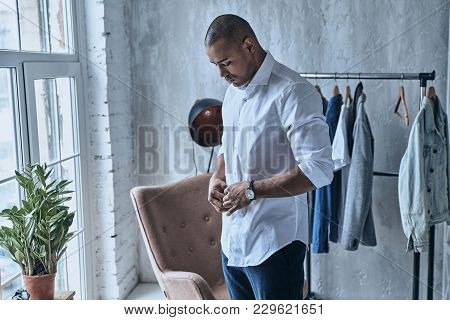 Paying Attention To Every Detail. Handsome Young African Man Buttoning His Shirt While Standing At H