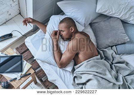 So Hard To Wake Up. Top View Of Young African Man Massaging Nose While Lying In The Bed At Home