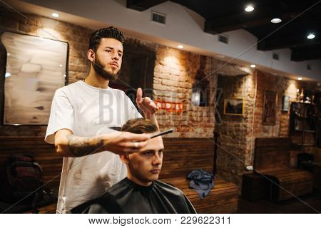 Creating New Hair Look. Making Haircut Look Perfect. Young Bearded Man Getting Haircut By Hairdresse