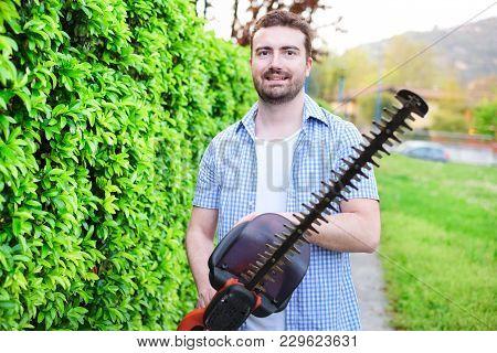 Hobbyist Gardener Using An Hedge Clipper In His Home Garden