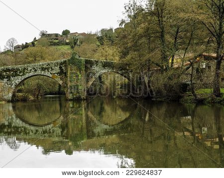 Reflections Of The Arch Of A Bridge And House In Allariz, Galicia. Spain