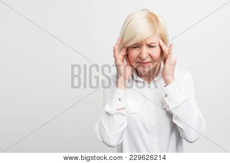 Sick And Old Woman Is Touching Her Head Showing She Has A Headache. Probably She Will Get Sick. Clos