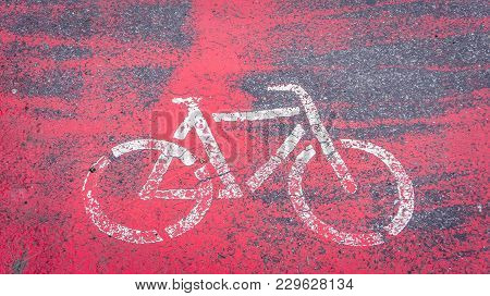 Painted In White On A Red Bicycle Background Showing A Bicycle Ride. A Sign Showing A Bicycle