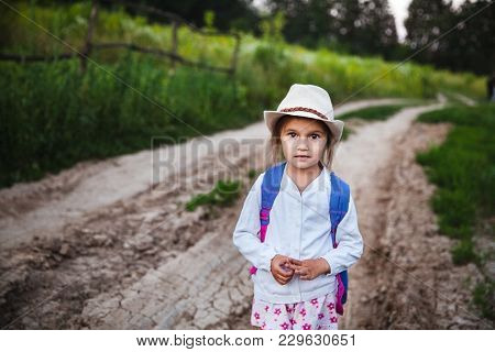 Little Beautiful Girl In Hat And Backpack In Nature A