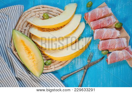 Deliciuos Italian Starter - Cantaloupe Melon, Parma Ham And Olives On Wooden Background