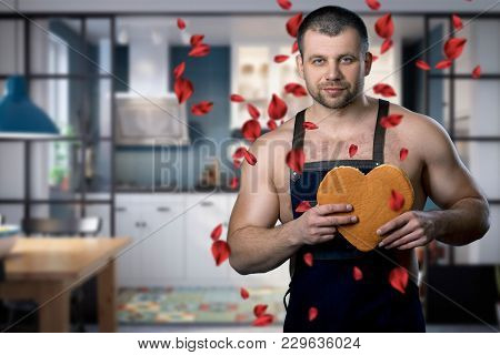 Handsome Man Standing In The Kitchen With A Biscuit Heart In His Hands. Rose Petals Falling On The M