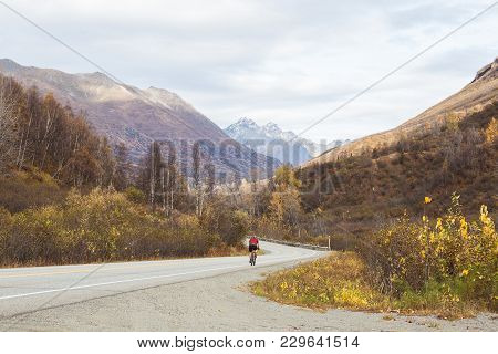 A Cyclist Biking Down A Road In The Alaskan Mountains In Autumn. Clouds Overhead, Double Yellow Line
