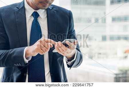 Close Up Hand Of Businessman Using Mobile Phone Near Office Window At Office Building,online Busines