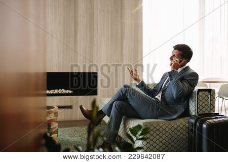 Entrepreneur Sitting At Airport Business Lounge And Talking On Cellphone. Businessman Waiting For Hi