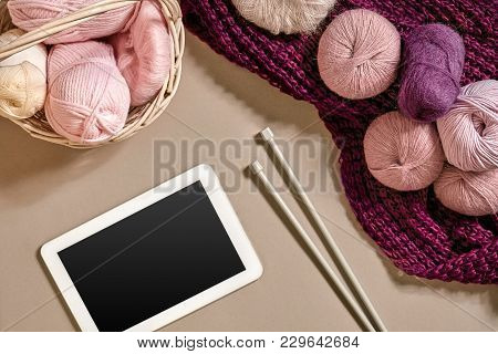Pink And Purple Balls Of Wool Threads With Knitting Needles Lying In Basket On Beige Background. Moc