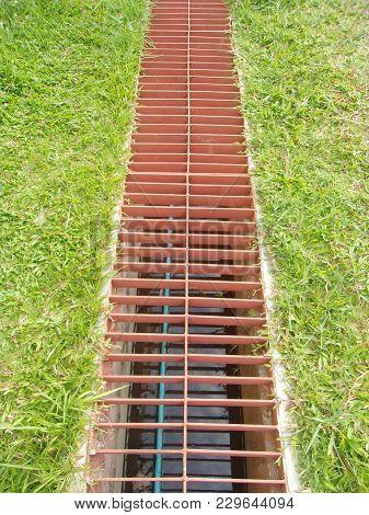 Waterway And Grass. Iron Grate Of Water Drain In Grass Garden Field.