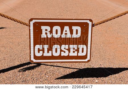 Hanging Road Closed Sign From A Rope With Shadows Cast On The Resurfaced Road