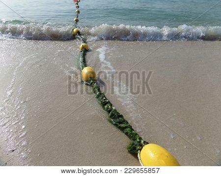 A Row Of Yellow Buoy Markers On A Sandy Beach. Dubai.2018