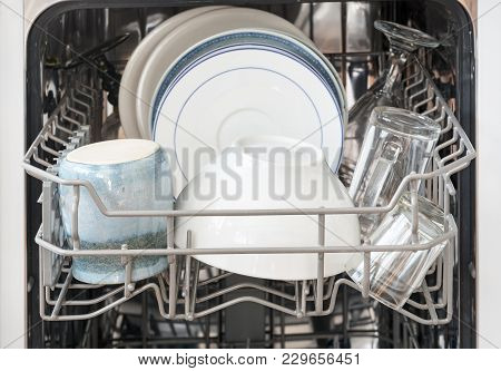 Dishes In The Basket Of A Dishwasher, Ready For Cleaning, Selected Focus, Very Narrow Depth Of Field