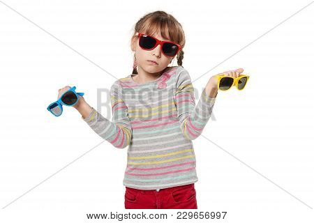 Embarrassed Child Girl Holding Multicolored Sunglasses Shrugging Shoulders, Isolated On White Backgr