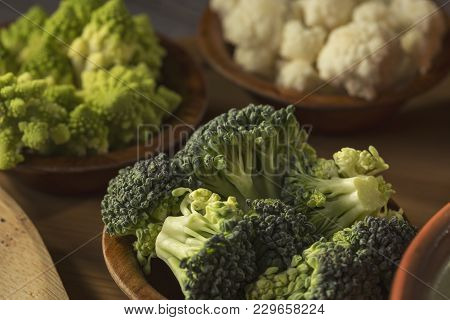Fresh Pieces Of Broccoli, Romanesco Broccoli And Cauliflower In Small Rustic Wooden Bowls. Selective