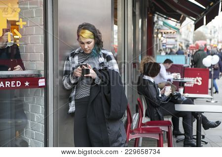 London - September 27, 2016: Women With Color Hair  Buried In The Phone, Waiting For The Subway Arou
