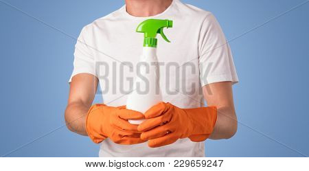 Housekeeper with cleaning product and equipment in front of a blue empty wall