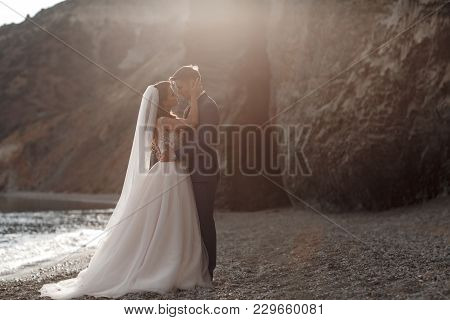 A Beautiful Bride And Groom On Their Wedding Day Walk Along A Rocky Shore Near The Sea.young Couple