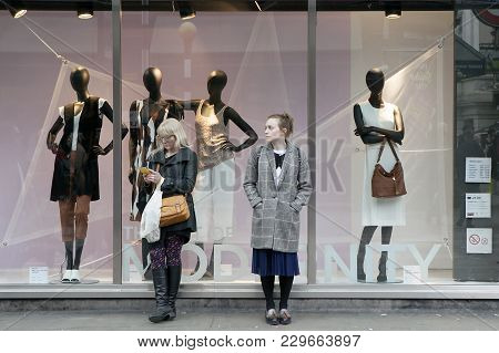 London - October  27, 2016: Two Women Are Standing At The Shop Window, Waiting For Friends