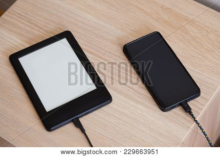 Two Mobile Devices, Cellphone And Ebook, Connected With Power Cables To Get Charged  On A Wooden Fur