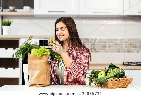 Lovely Slim Woman, In Checked Red Shirt, Unpacking Shopping Bag With Green Food Near Basket With Gre