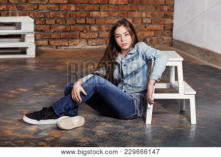 Brunette Hipster Teenager Sitting Floor. Stylish Adolescent Girl Wears Casual Clothes, Jeans Jacket.