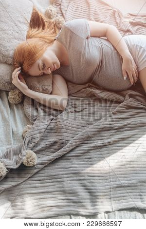 Beautiful Pregnant Woman Laying On Bed And Holds Hands On Belly In Bedroom At Home. Pregnancy, Paren