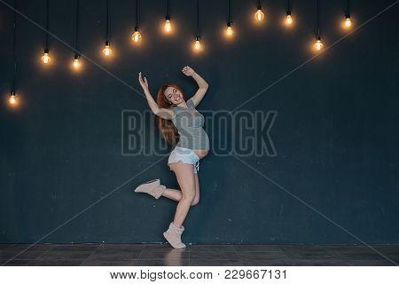 Future Mom Having Fun, Jumping Like A Ballerina. Cheerful Healthy Pregnant Woman On Dark Gray Backgr