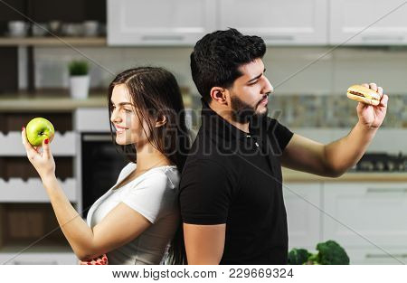 Attractive Dark-haired Man In Black T-shirt And Brunette Girl Hesitating Between Green Apple And Tas