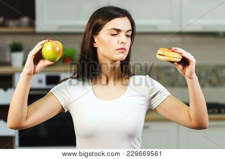 Attractive Long-haired Woman In A Good Shape Hesitating Between Fresh Apple And Unhealthy Hamburger,