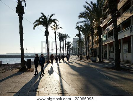 Torrevieja, Spain - February 17,  2018: People Walking By The Seafront Of Torrevieja. Costa Blanca.