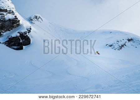 Skier Descends From The Mountain, Freeride In The Snowy Mountains
