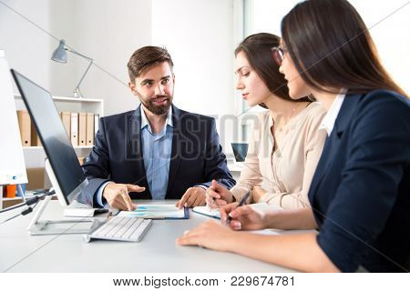 Serious businessman explains to colleagues a new project
