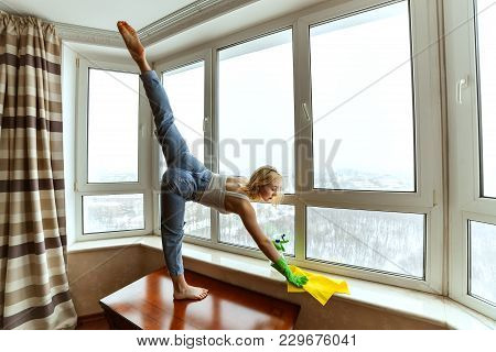 Woman Does Gymnastics While Cleaning In The Apartment, She Washes The Windows.