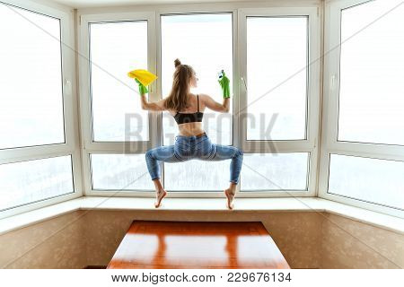 Woman Washes Windows In A Yoga Pose, She Is Doing Sports While Cleaning An Apartment.
