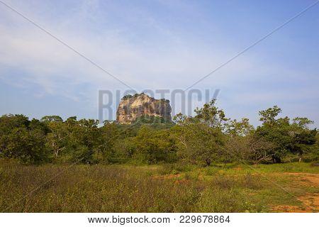 Historic Sigiriya Rock In Sri Lanka With Woodland And Scrub On Red Sandy Soil Under A Blue Cloudy Sk