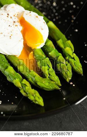 Green Boiled Asparagus With Poached Egg, With Salt And Spices On Black Plate