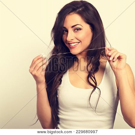 Happy Smiling Woman Cleaning The Teeth The Dental Floss. Dental Hygiene. Toned Closeup Portrait