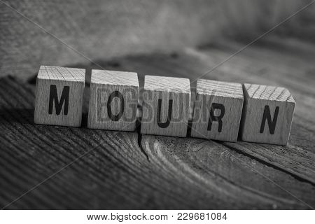 Macro Of The Word Mourn Formed By Wooden Blocks On A Wooden Floor