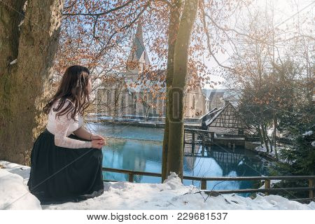 Blue Water Lake And A Girl Admiring It - Young Attractive Woman, In A Squat Position, Enjoying The V