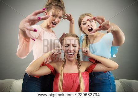 Woman Being Bullied By Her Two Female Friends. Women Having Argument. Angry Fury Girls Screaming At