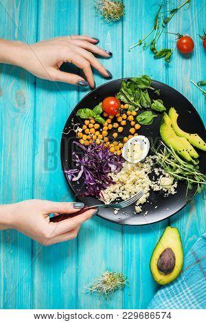Woman Hands And Healthy Vegan Lunch Bowl. Vegan Buddha Bowl. Vegetables And Nuts In Buddha Bowl On B