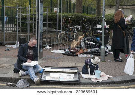 London, England - July 12, 2016 Beggar Draws On The Album. His Dog Sits Nearby. Columbia Flower Mark