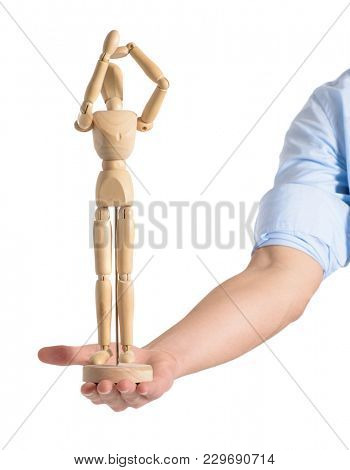 Close-up Of Hand Holding Wooden Dummy Over White Background